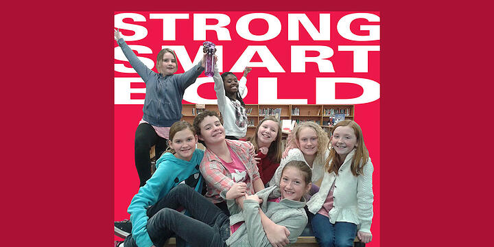 eight girls posing enthusiastically with the words strong, smart, bold in the background