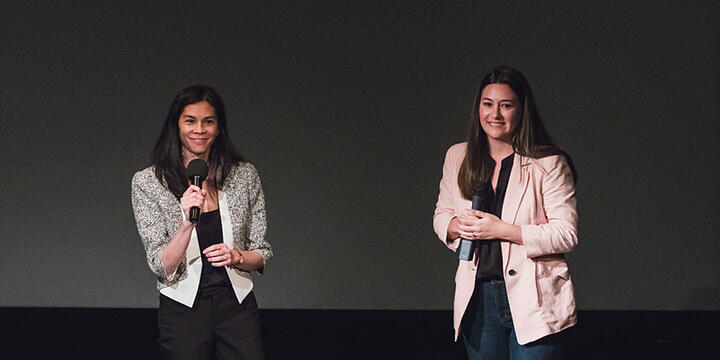 Jessamine Chin and Erin Baudo Felter on a stage holding microphones