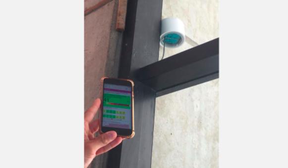 smartphone held near an air quality sensor