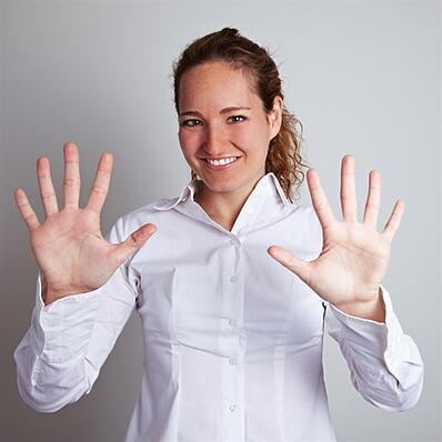 woman holding her hands out with ten fingers outstretched