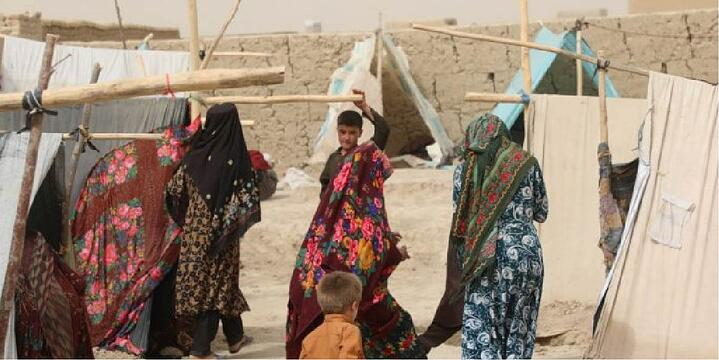Women walk among makeshift tents in a camp for internally displaced people in Mazar-e Sharif city in northern Afghanistan