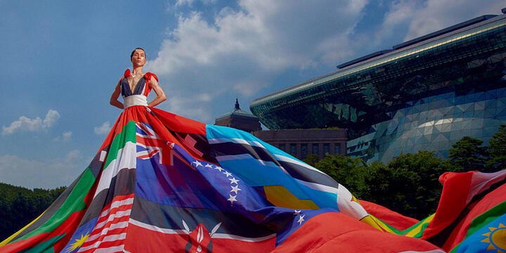 model standing in front of Seoul city hall wearing the rainbow dress just described