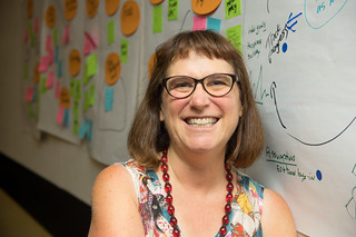 Beth Kanter sitting next to a wall with large sheets of paper and sticky notes
