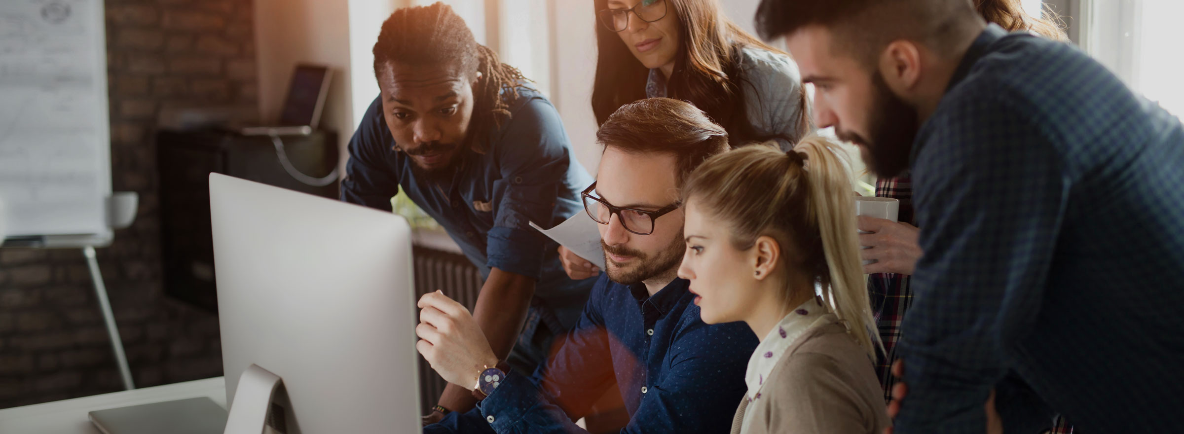 group of people looking with concern at a computer monitor