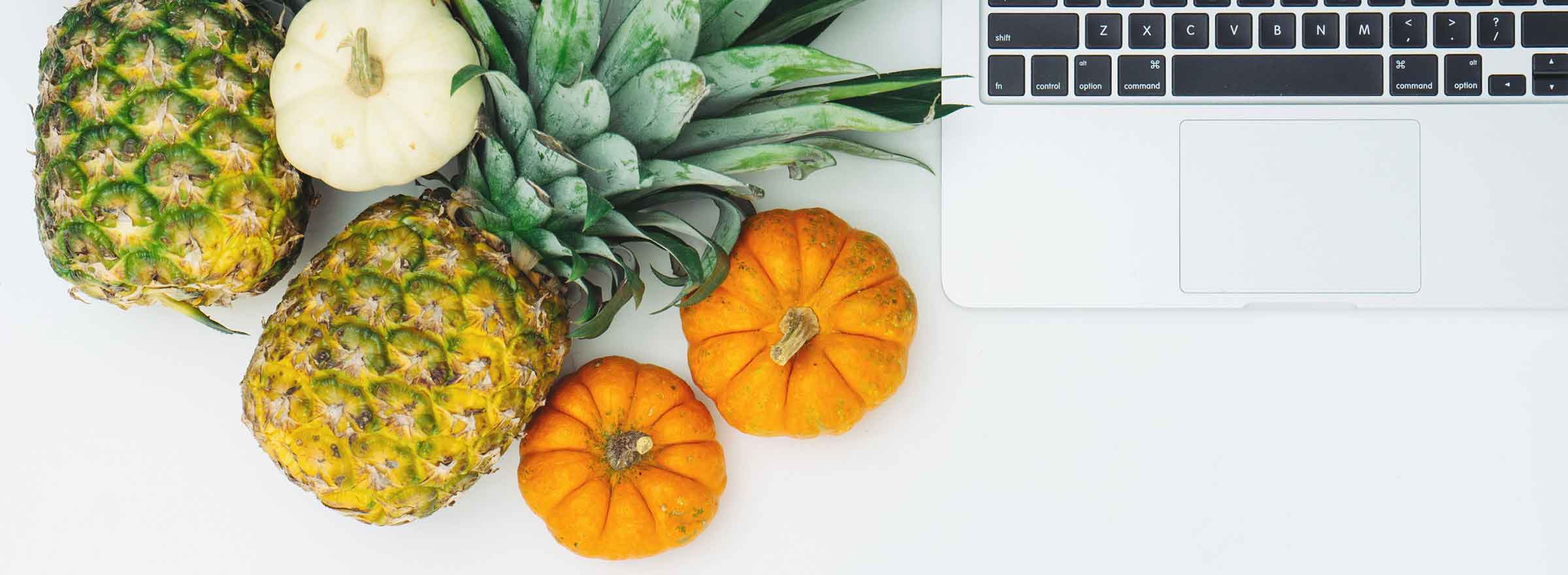 pineapples and pumpkins next to a laptop keyboard representing how Symantec helps nonprofits promote healthy eating