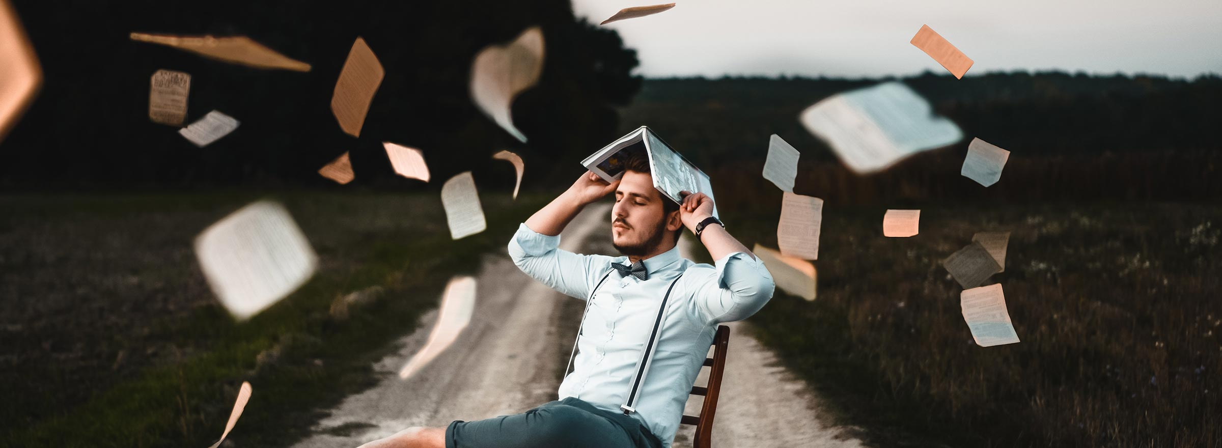 a man relaxing in a chair with his eyes closed and an open book on his head while papers flutter all around him, symbolizing that ignorance is not bliss for nonprofit accounting