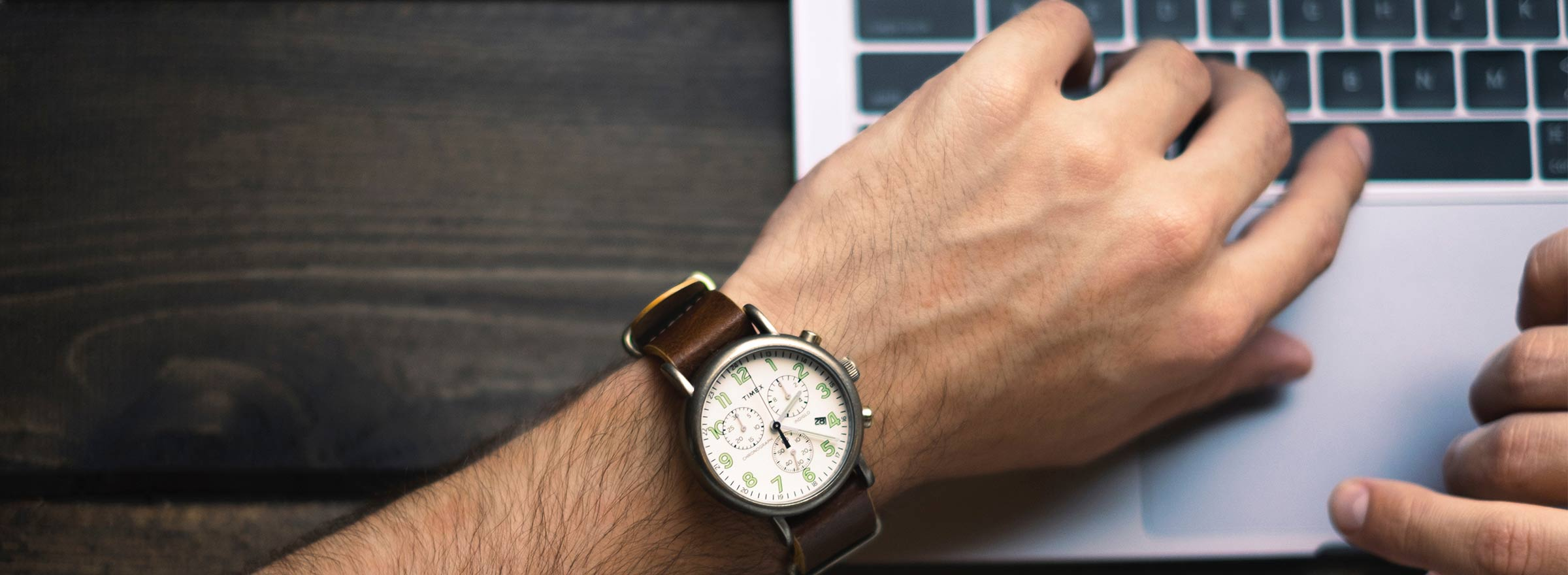 person looking at a wristwatch on a laptop keyboard, representing how nonprofits can save time and money with cloud integrations