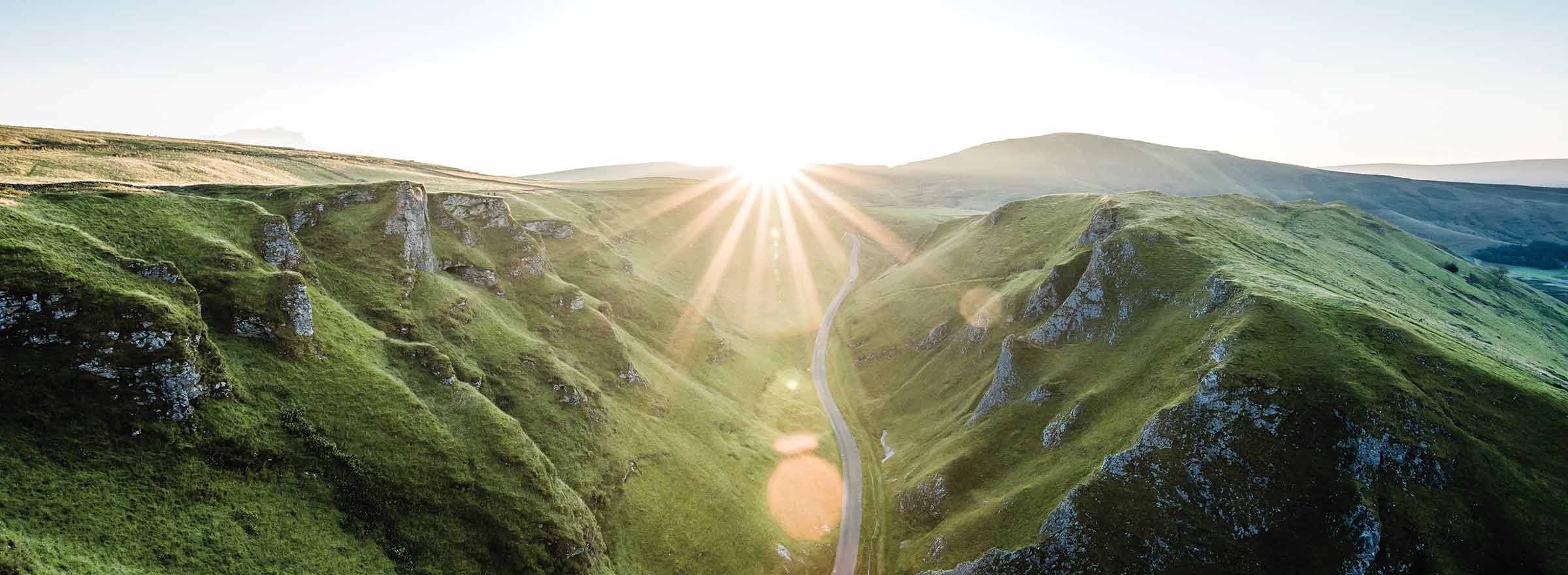 sunlight shining on a road that leads between grassy hillsides, representing the benefits to the environment of the TechSoup Refurbished Hardware Program