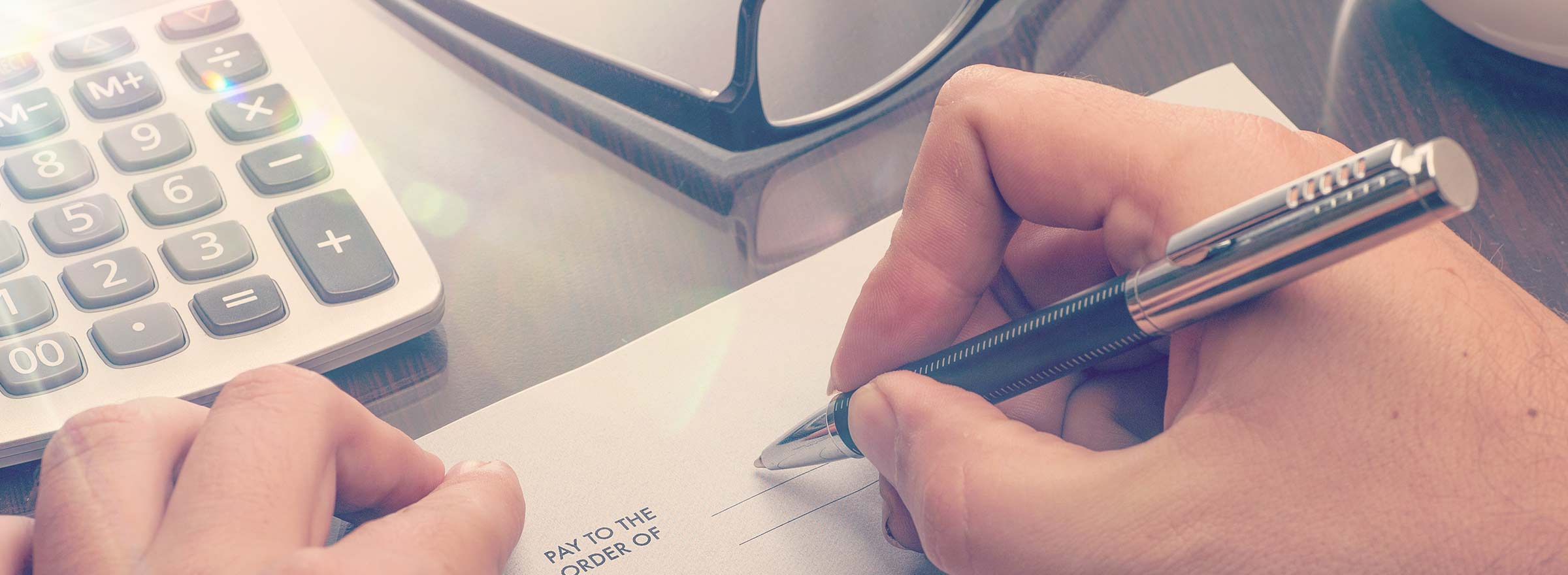 nonprofit staff member writing out a check by hand next to a calculator, representing the need for using adp to process payroll