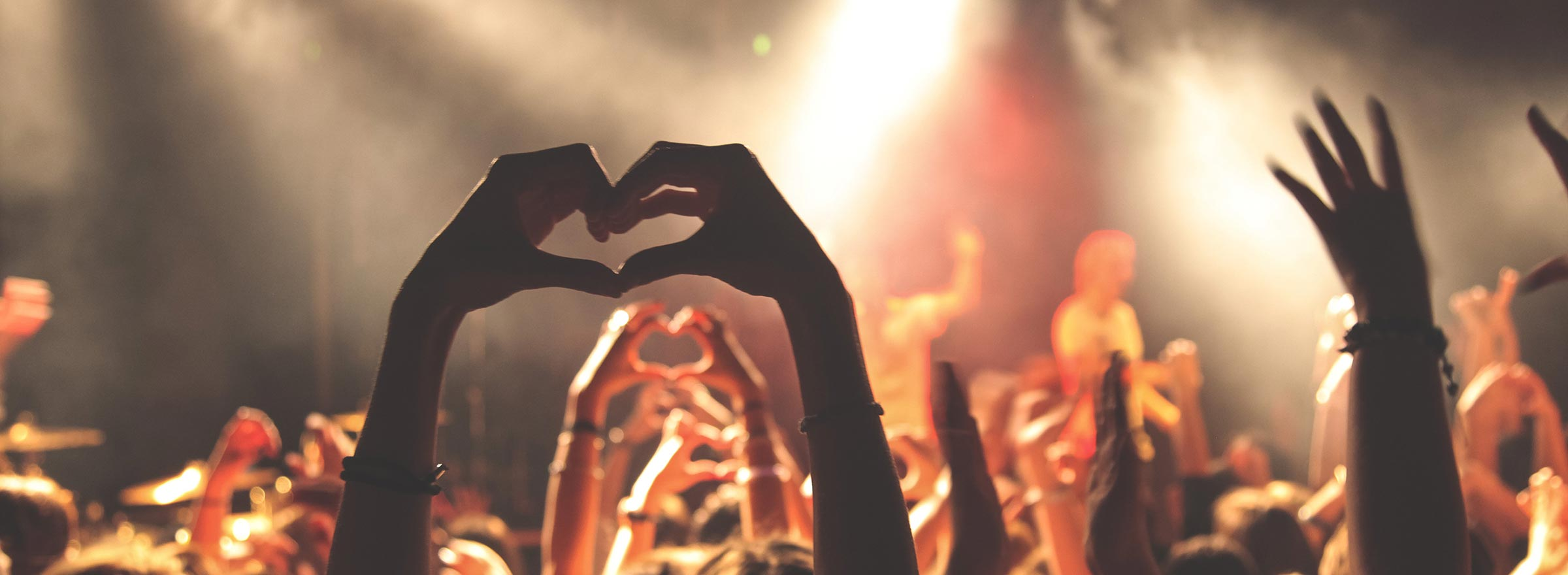 people at a concert holding up their hands in the shape of a heart, representing millennials and their potential to support nonprofit causes and fundraising