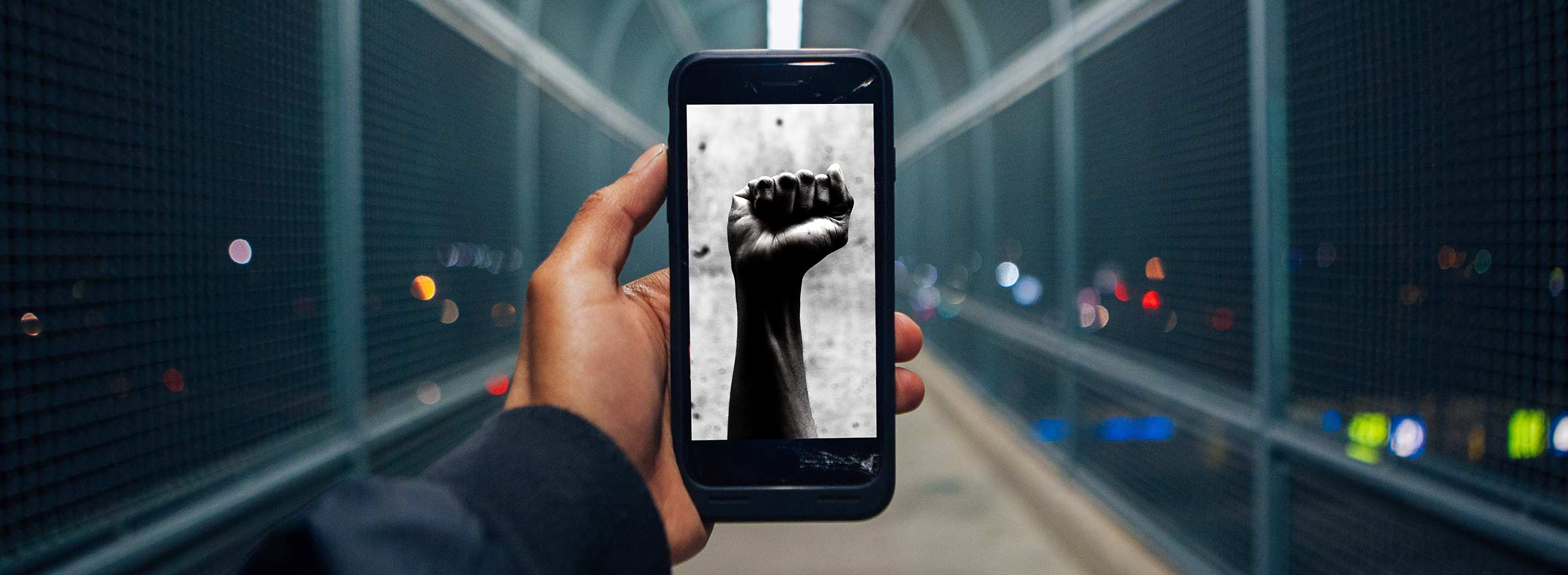 person looking at an image of a raised fist on a phone, symbolizing how public good app house is empowering positive social change
