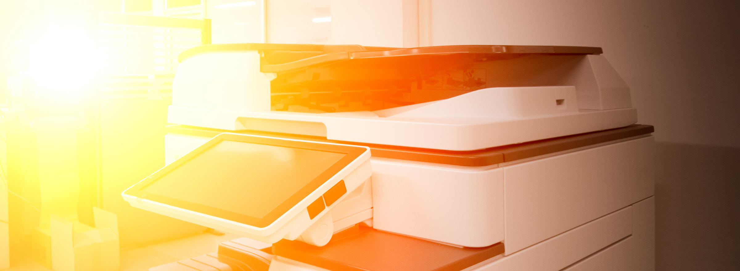 a copier bathed in sunlight, symbolizing the vulnerability of copiers to data theft and the need to keep nonprofit data secure