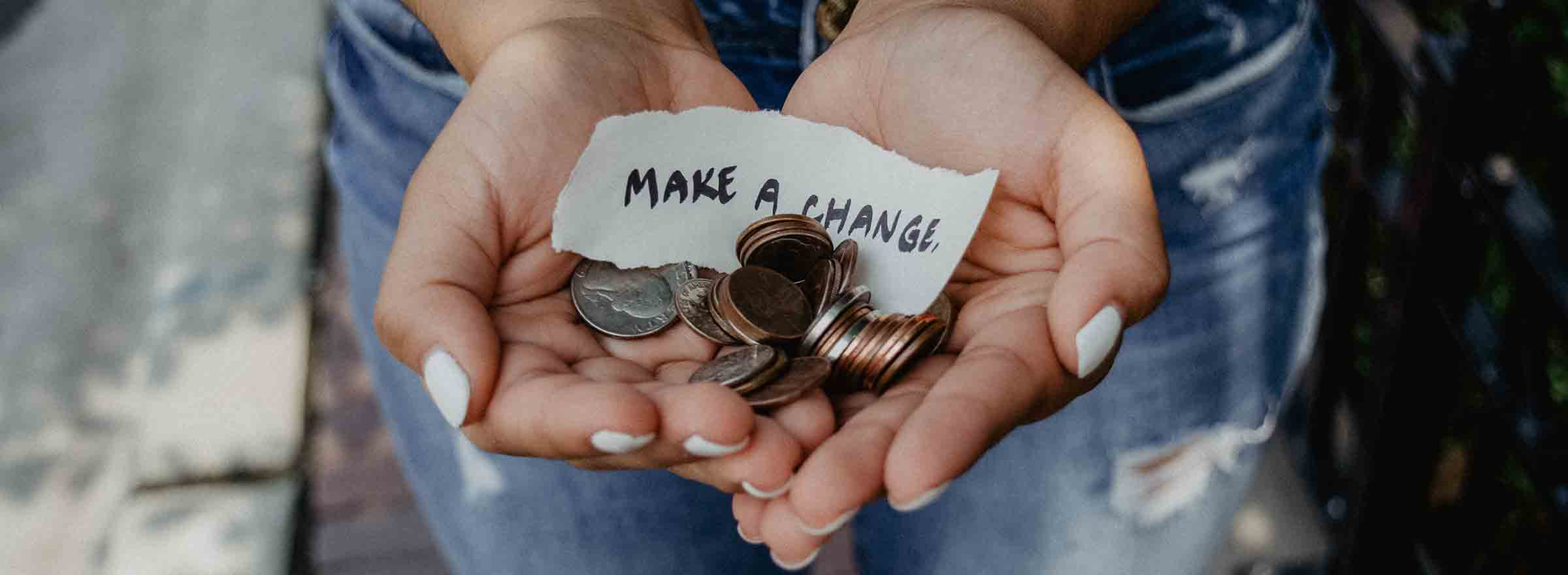 hands holding coins and a piece of paper that says make a change, representing the promise of monthly giving for nonprofit fundraising