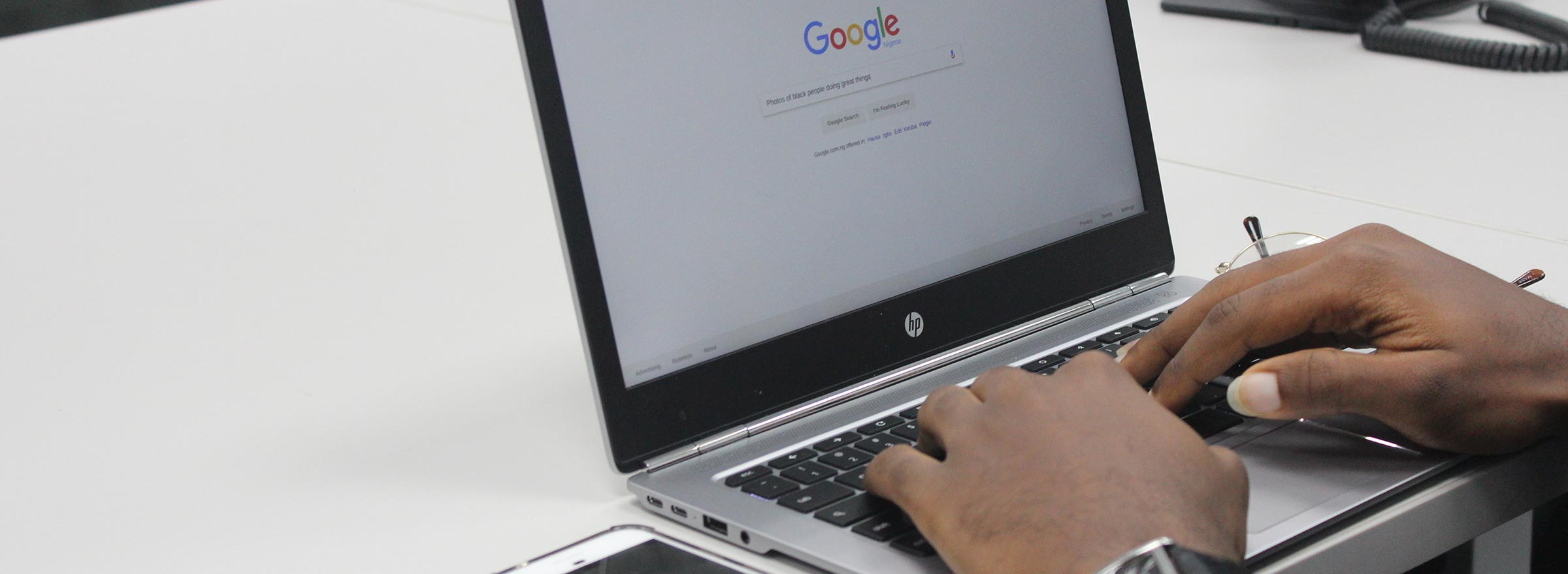 person typing on a laptop and searching via google, representing a nonprofit google adwords account