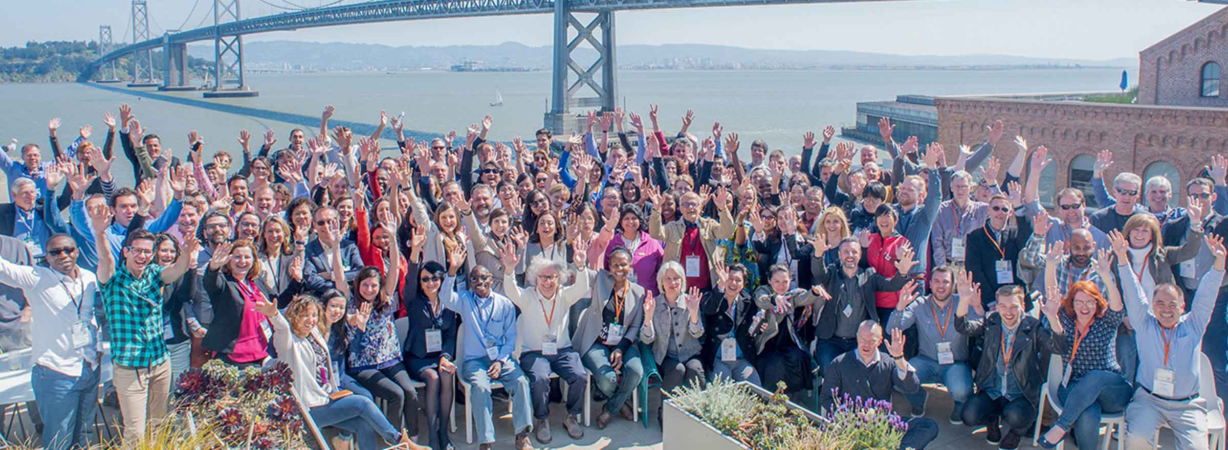 techsoup staff celebrating together in front of the bay bridge, representing the opportunity to invest in techsoup to build a more equitable planet