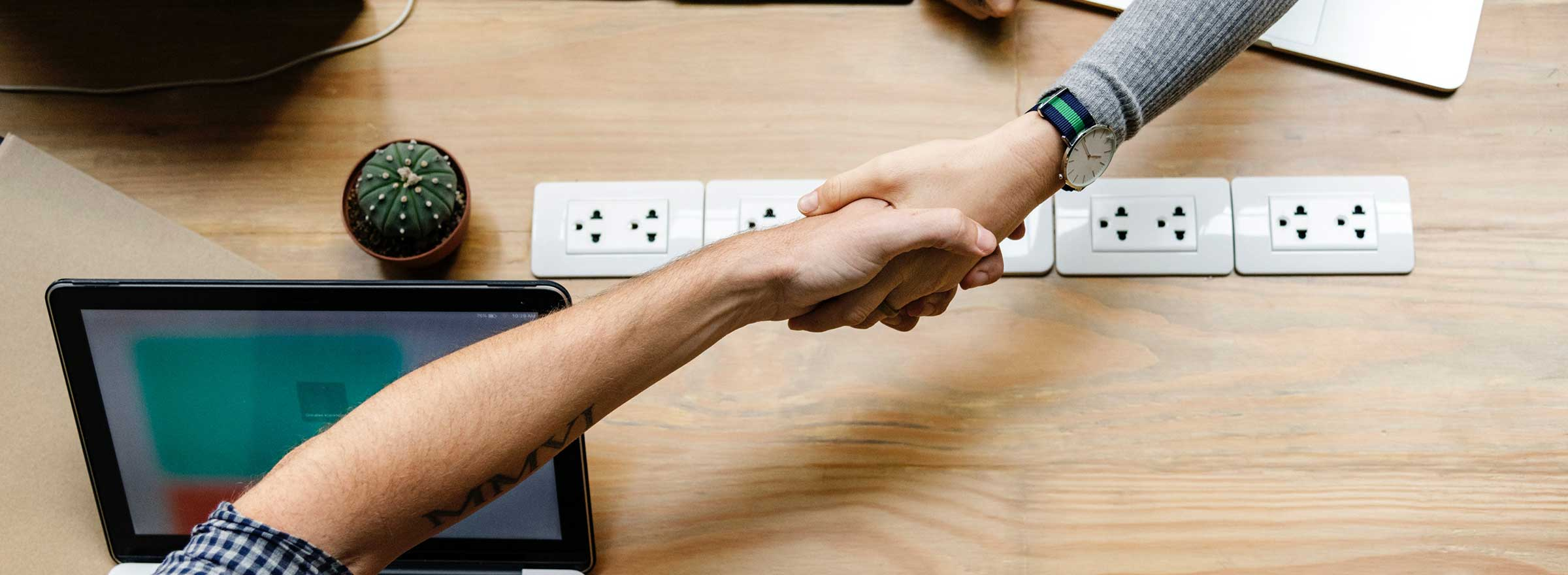 A hand from a TechSoup employee reaching a cross the desk to shake another hand