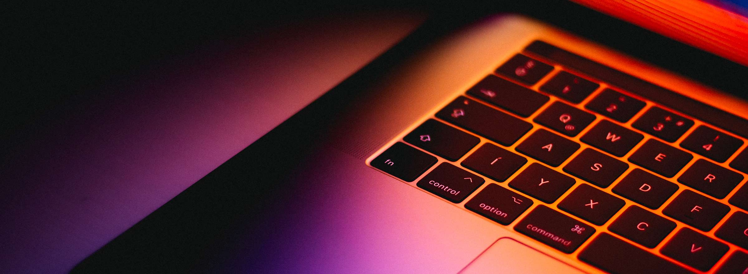 left third of a Mac laptop keyboard, in orange and purple light