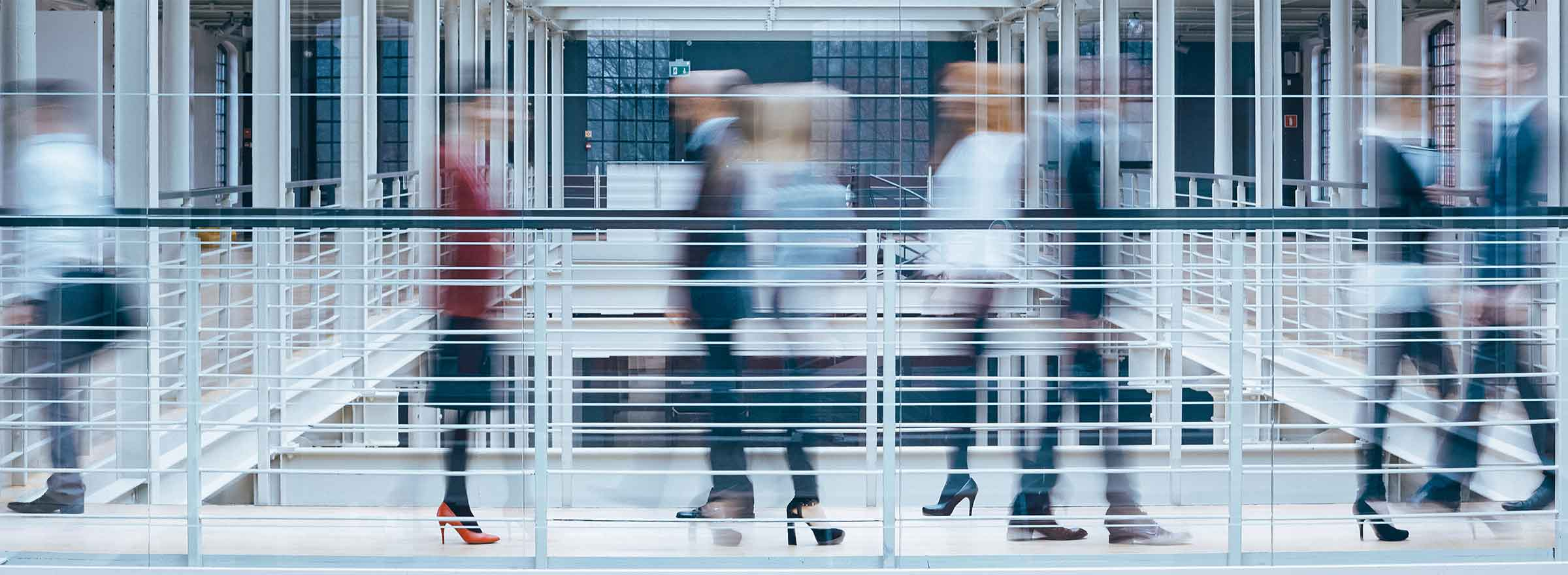 blurred images of people crossing a walkway over an atrium