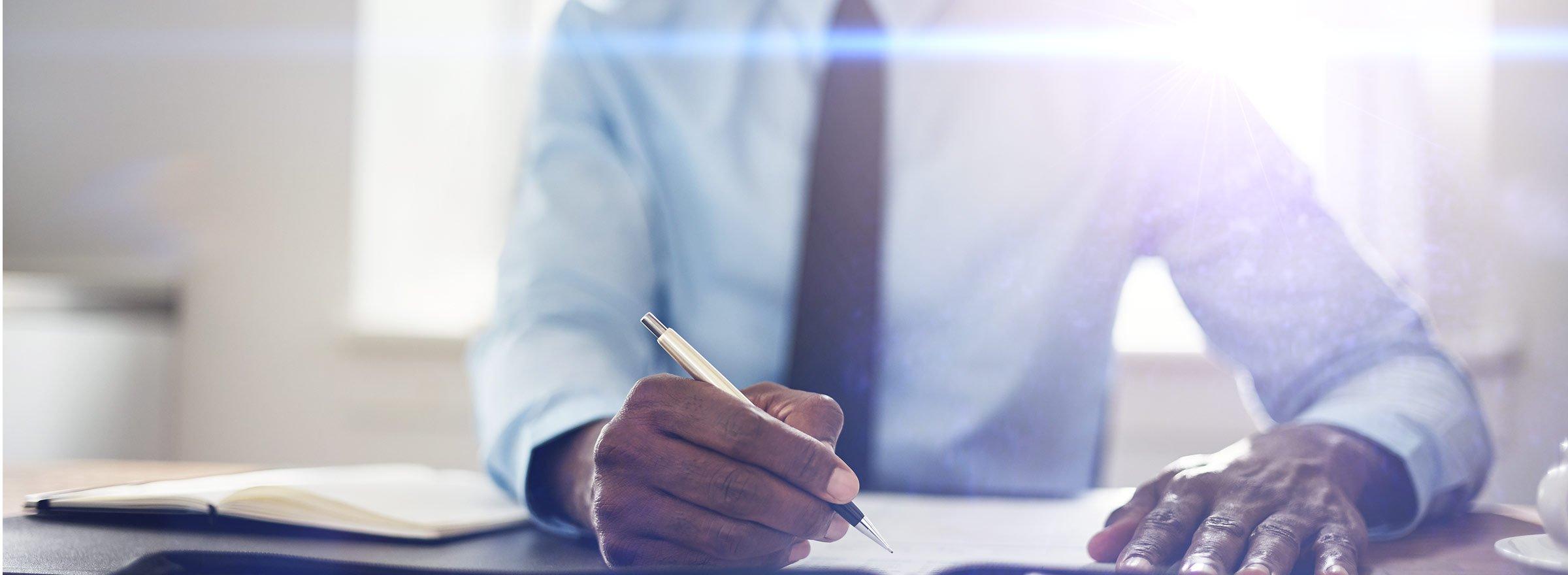 hands of a man holding a pen above a sheet of paper