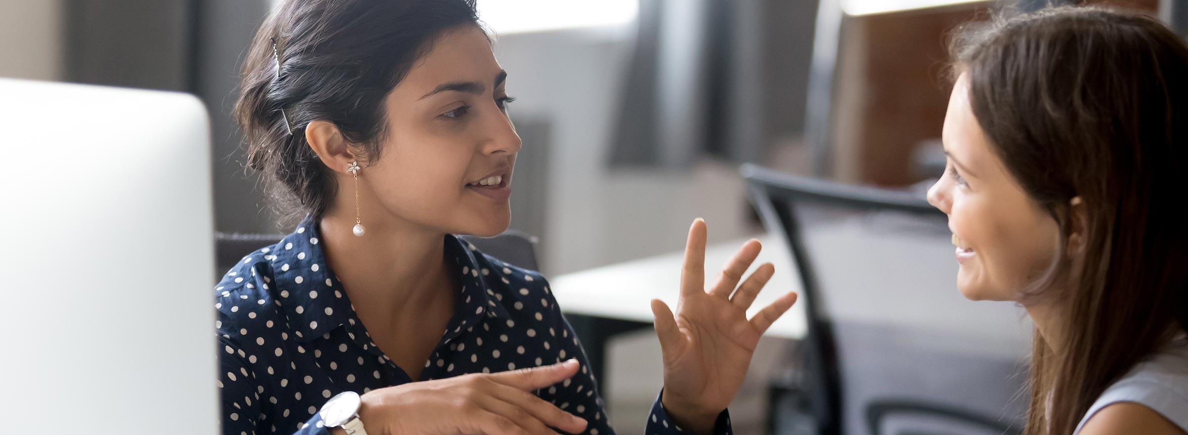 woman in workplace explaining something to another woman