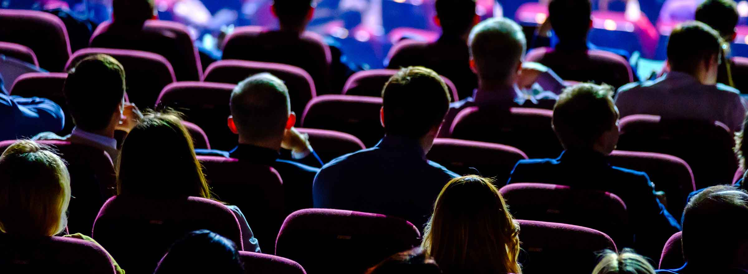 rear view of an audience in theater seating with light coming from in front of them