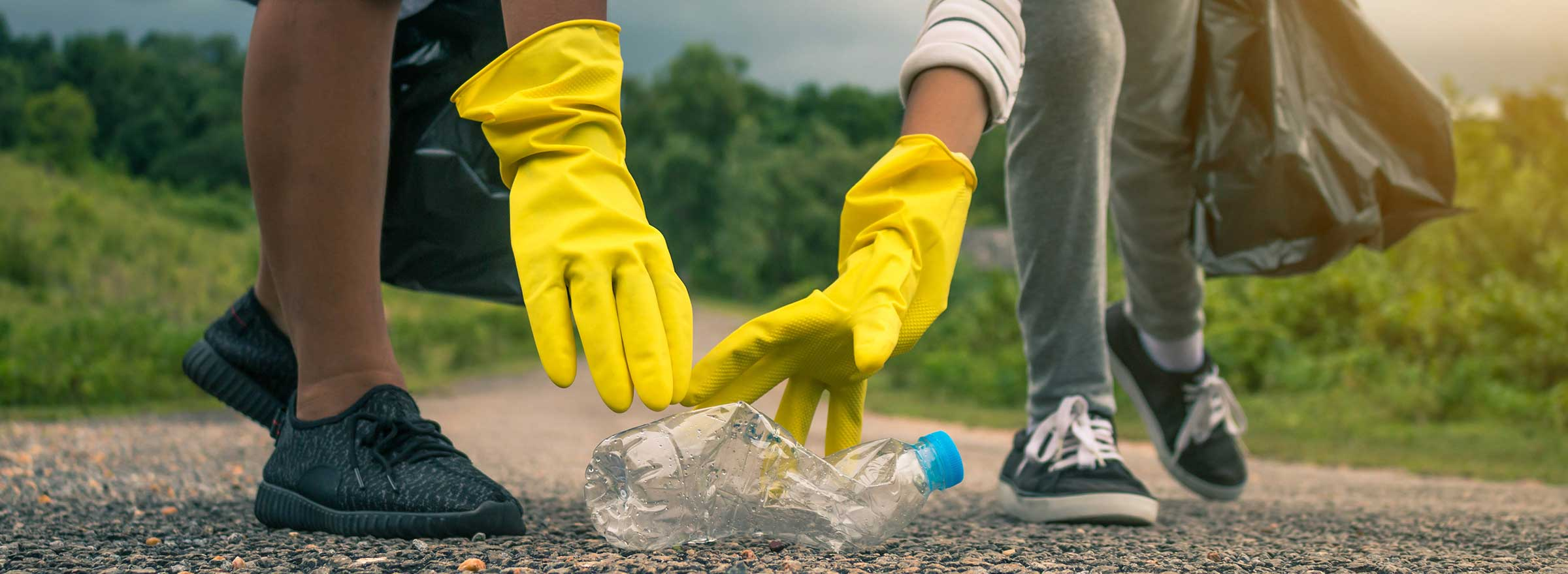 hands of two people with yellow gloves and carrying trash bags reach to pick up a crushed plastic bottle on the ground