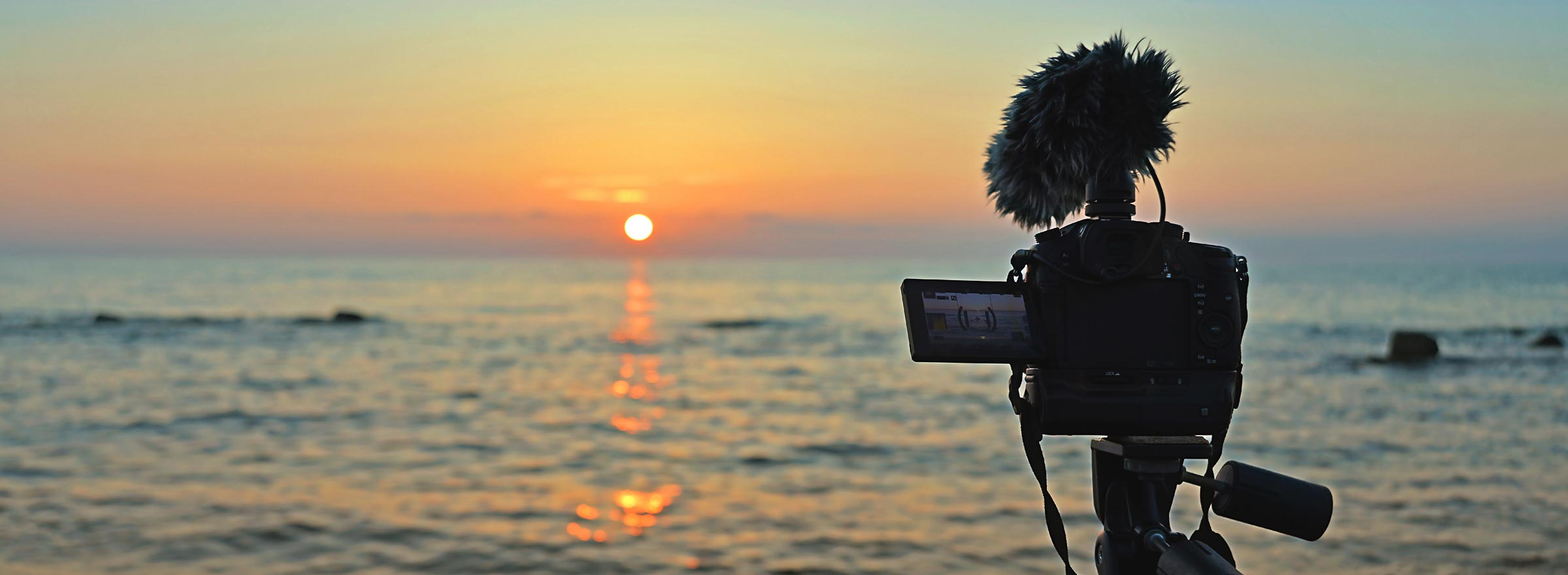 camera on tripod and supporting microphone points over the water to a setting or rising sun