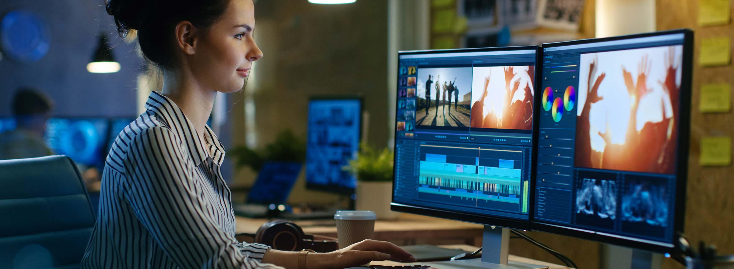 woman sitting in front of two computer screens and editing a video