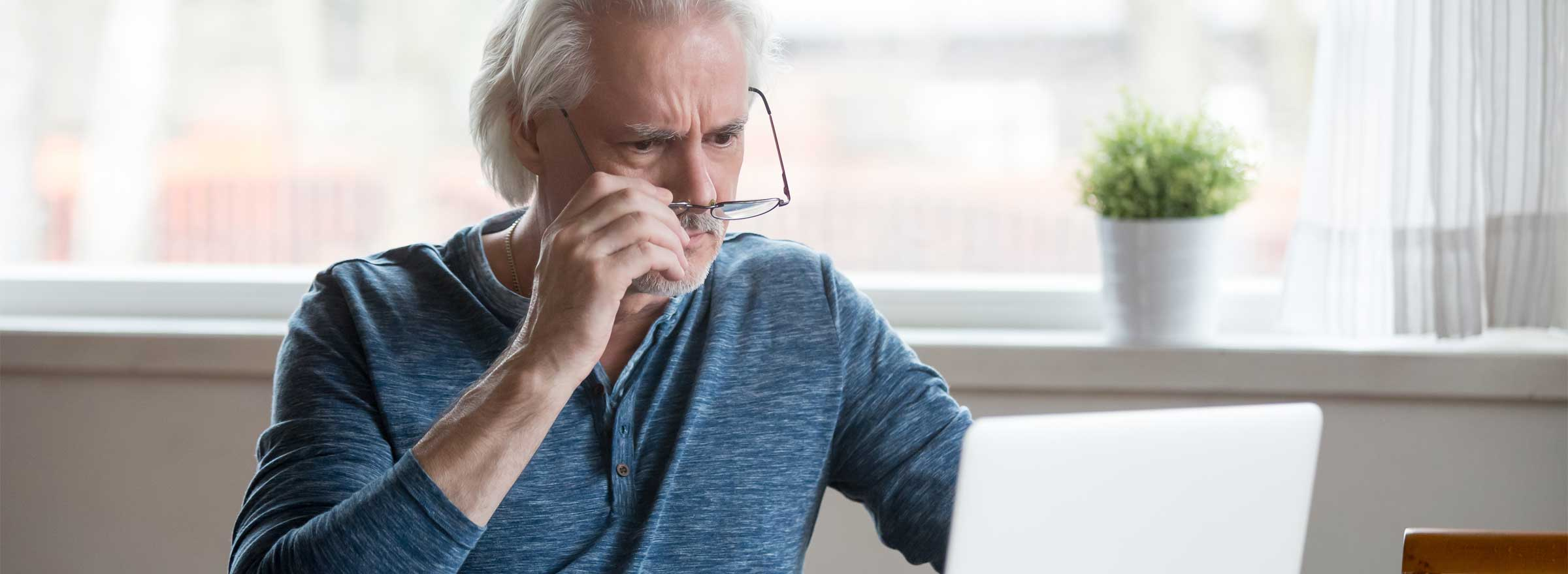 worried-looking man sitting in front of a laptop and taking off or putting on his glasses