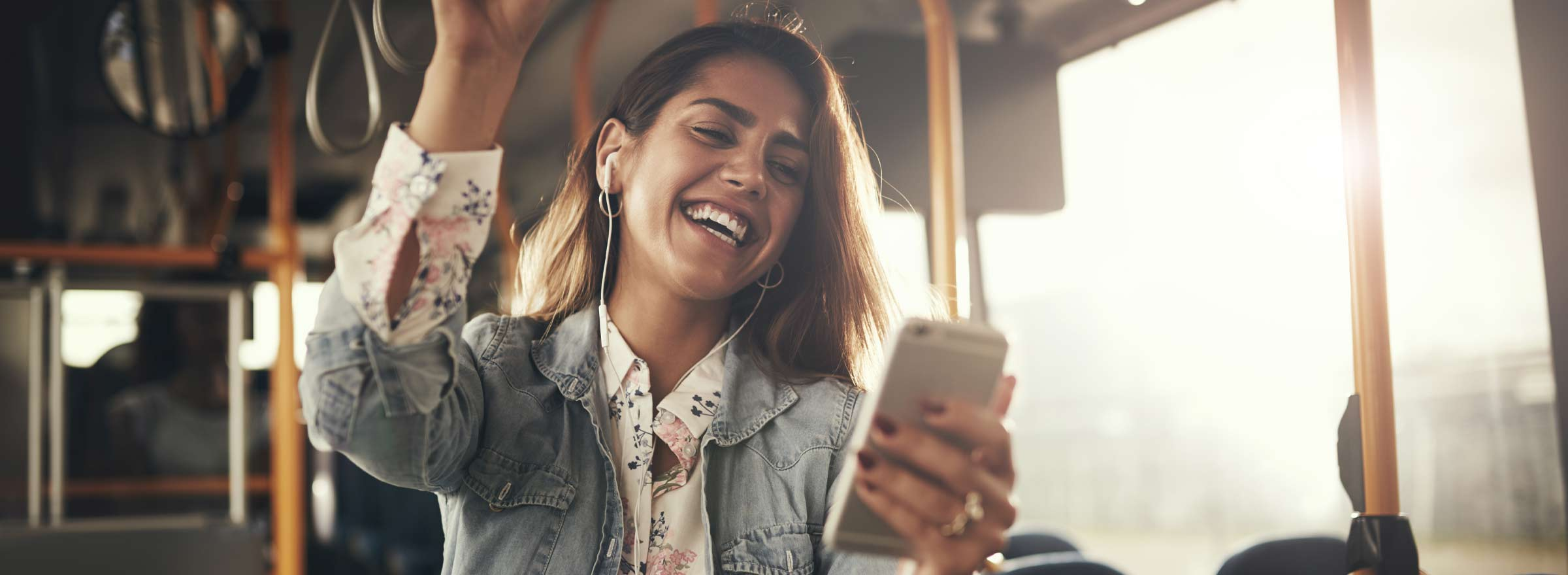 young woman standing on public transit looking at a smartphone and smiling