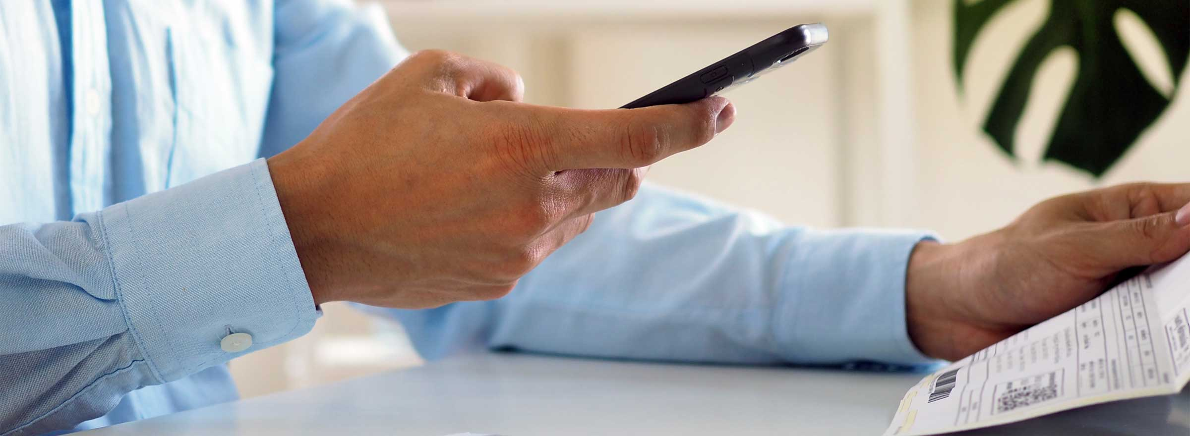 man's hands, one holding a document, the other on a smartphone
