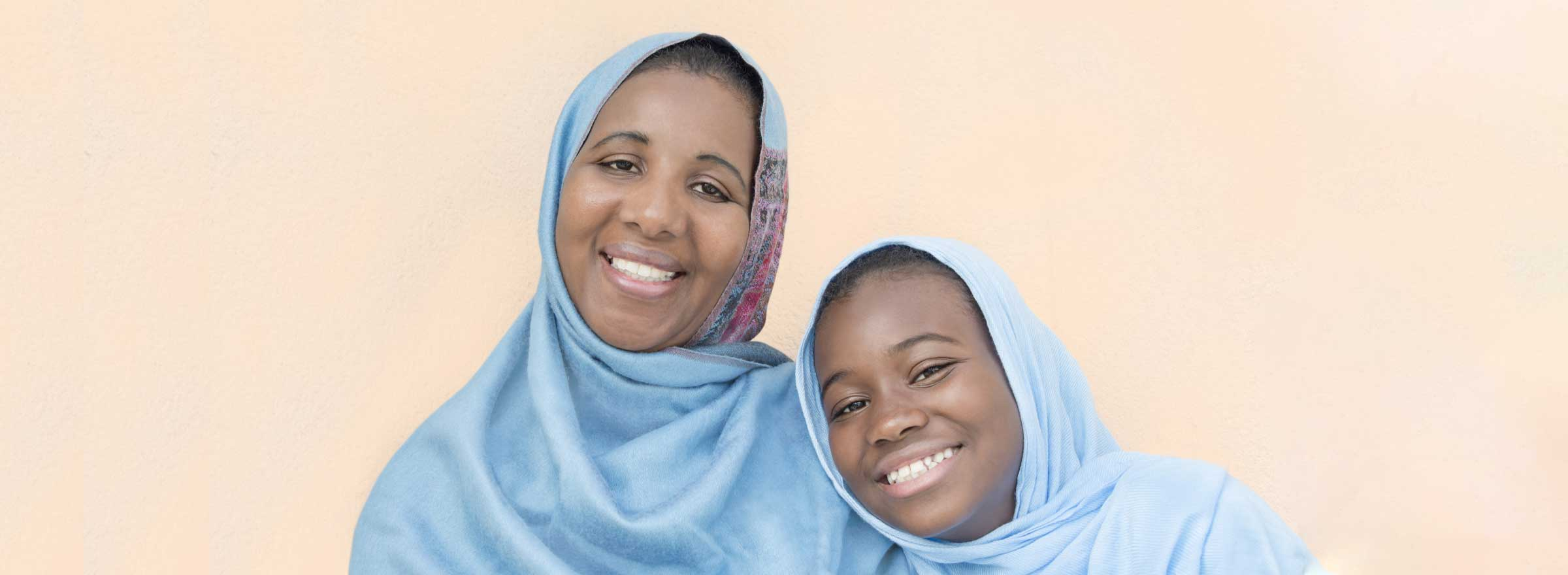 two smiling women wearing headscarves