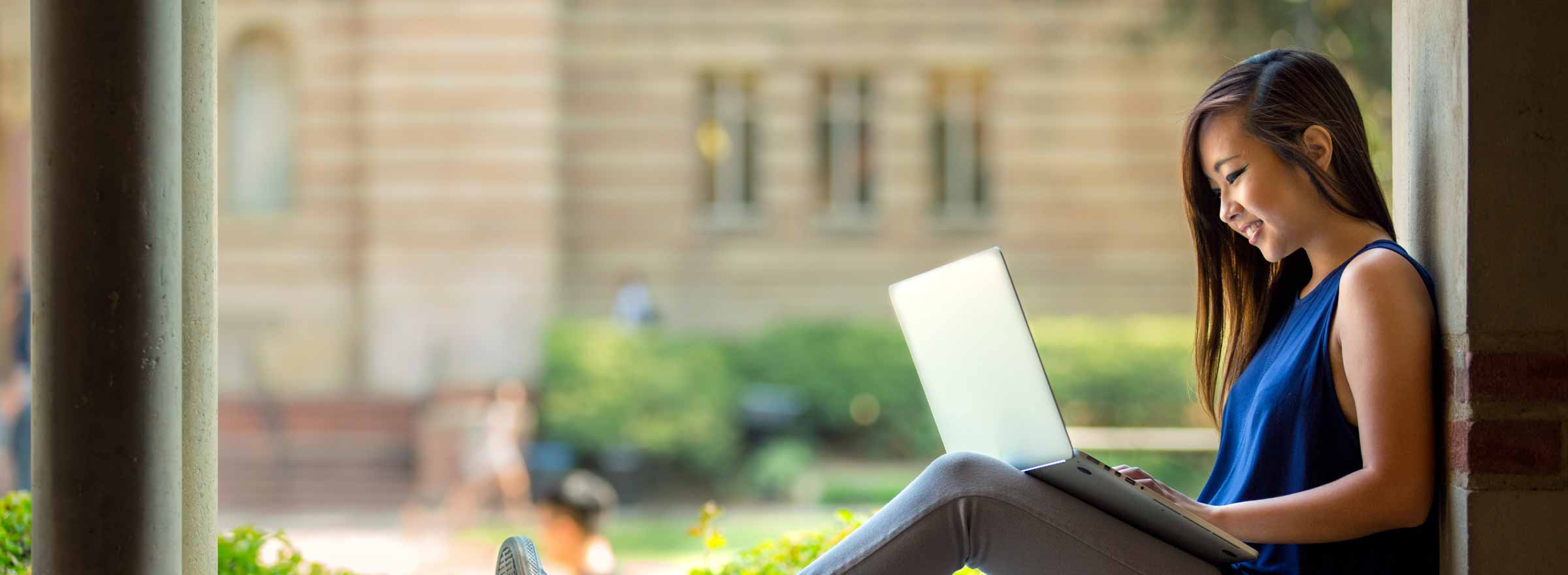 woman sitting in a library window using a laptop