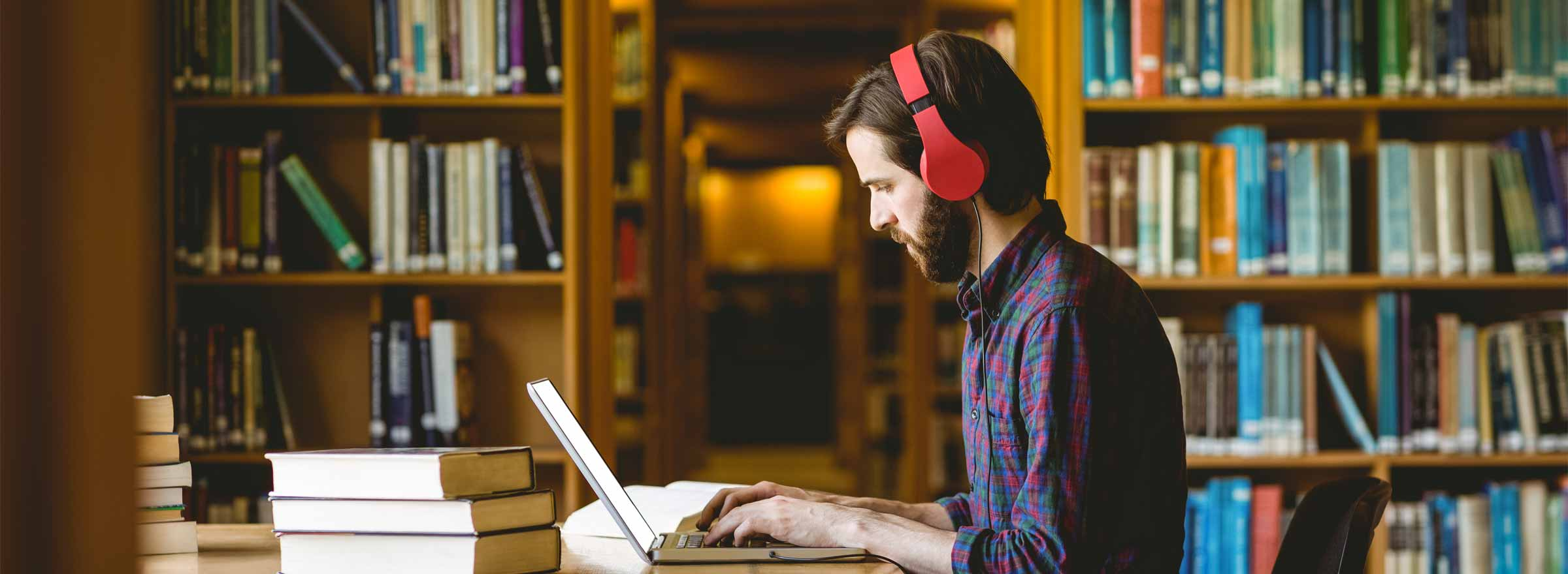man with headphones working on a computer in a library
