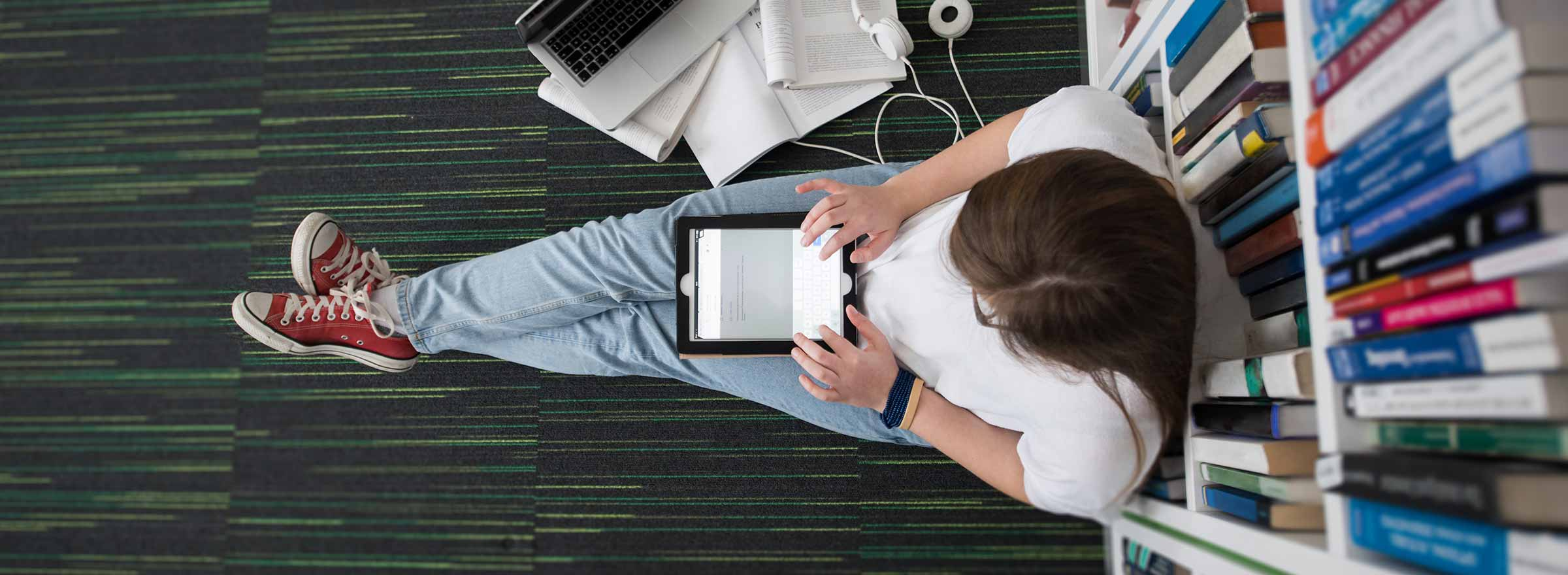 overhead view of a woman sitting leaning against bookshelves and using a tablet