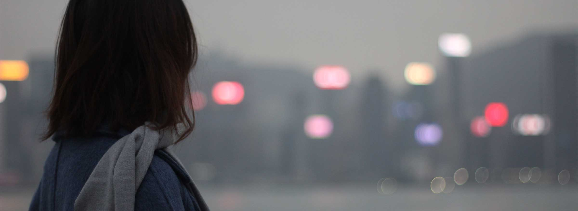 woman looking at distant blurred city lights