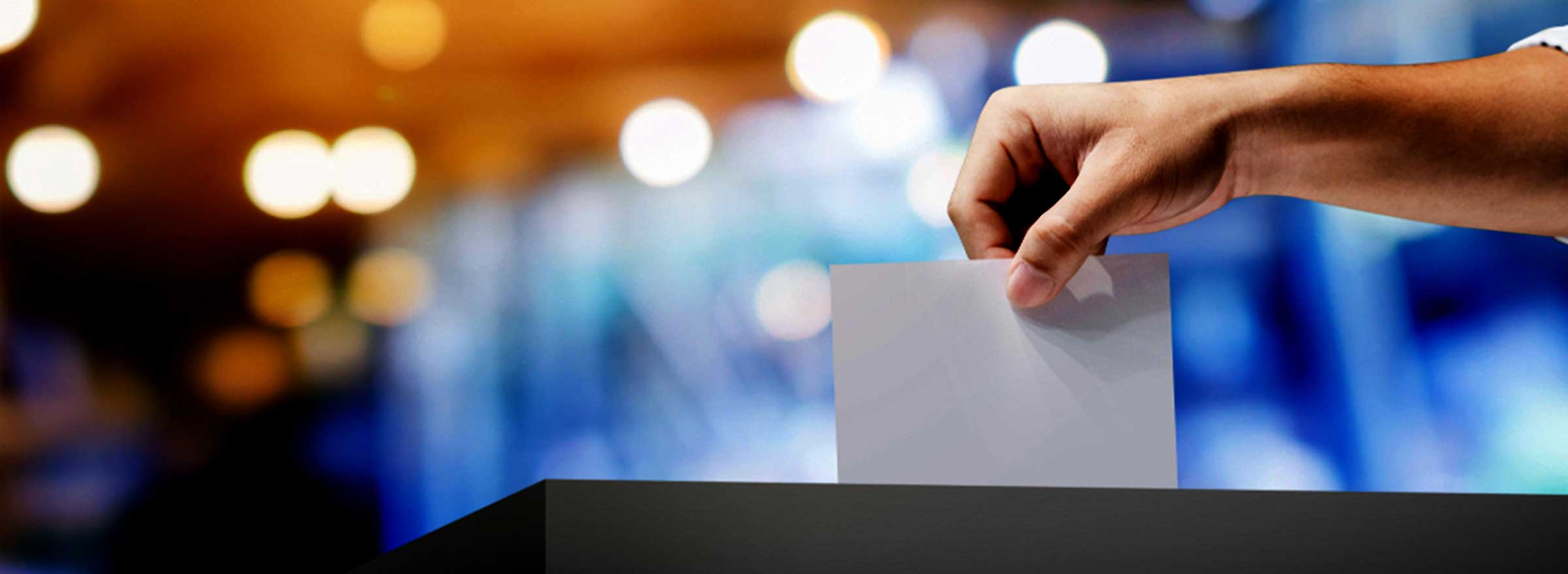 hand placing a ballot in a box