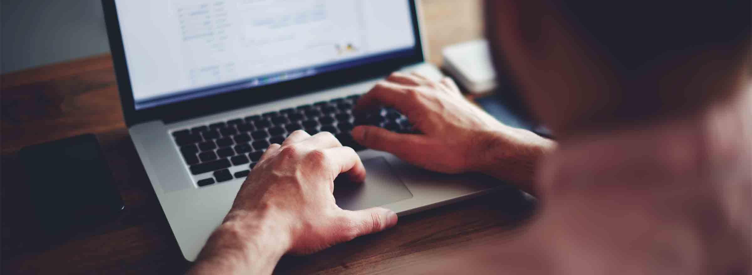 hands of a man using a laptop