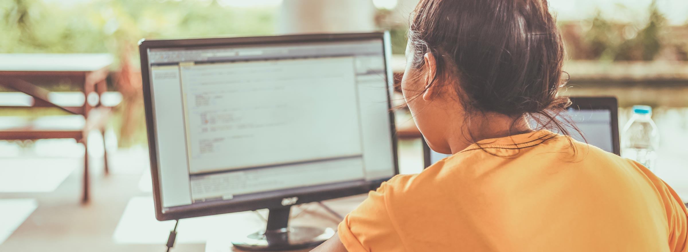 woman looking at code on a computer screen