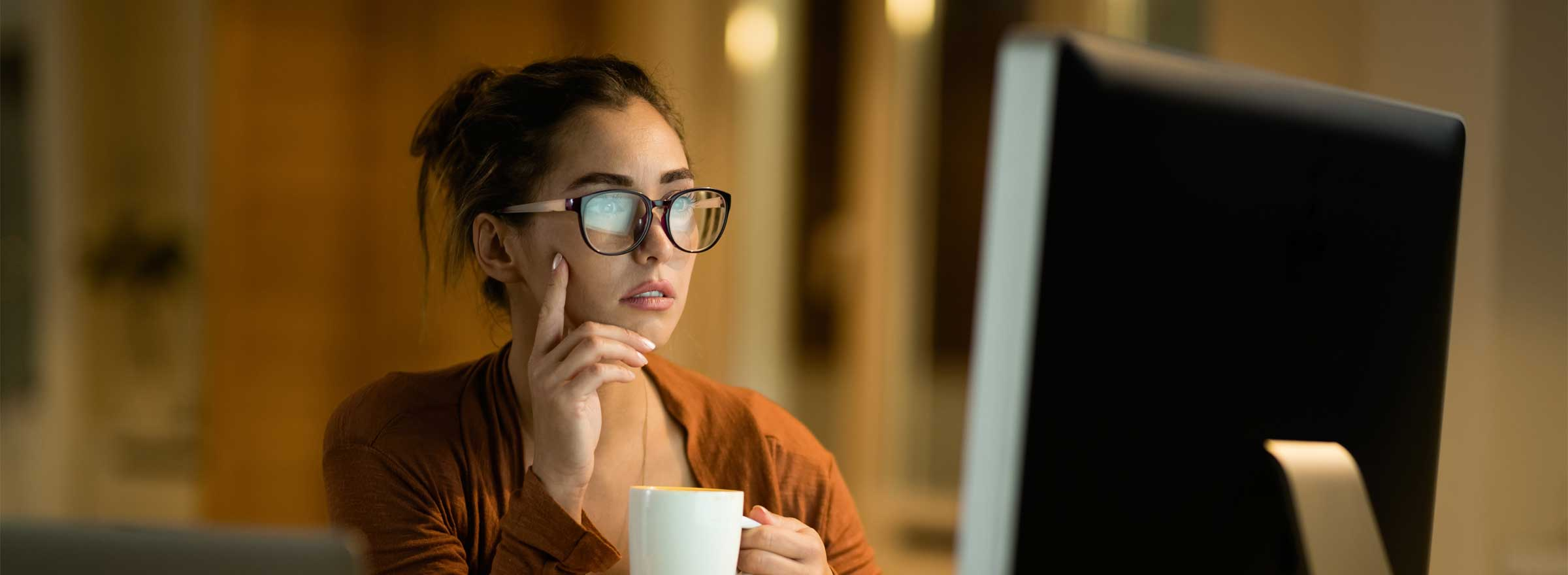 woman holding a mug and gazing at a desktop computer screen