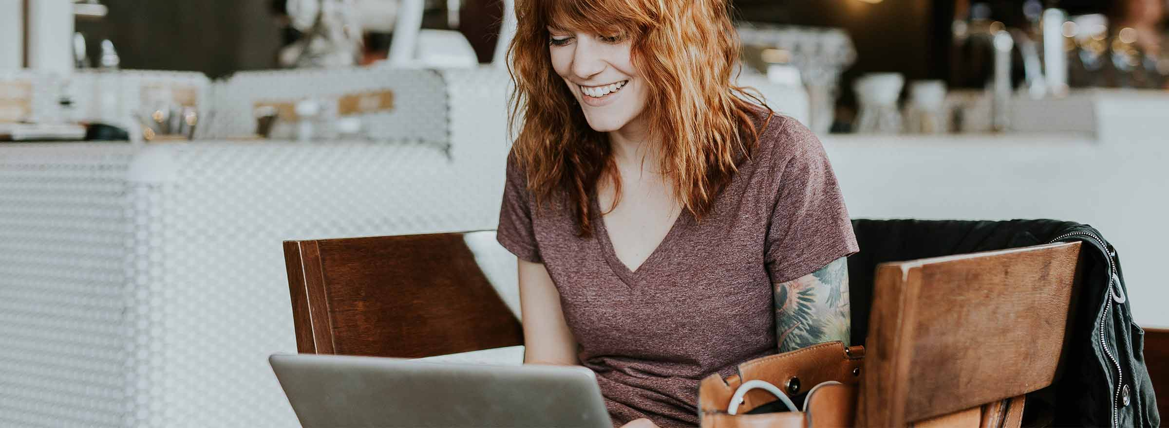 woman sitting on two facing chairs and using a laptop