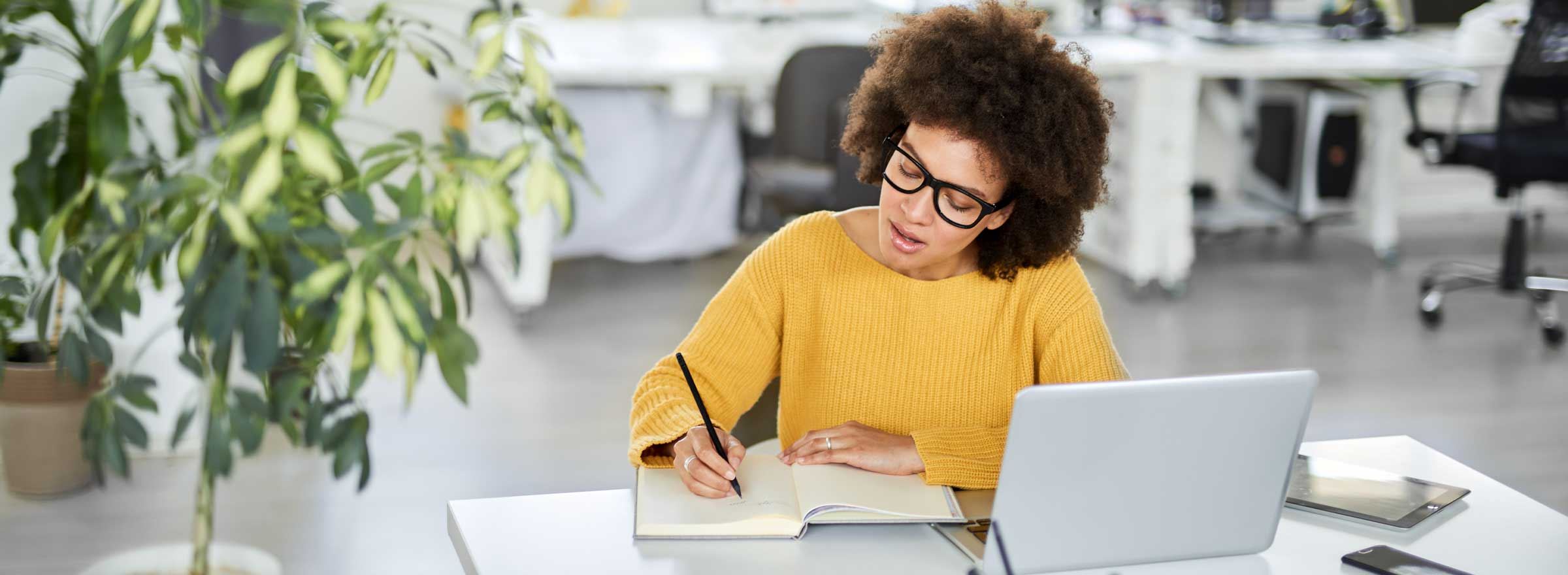 woman sitting at a laptop and writing in a notebook