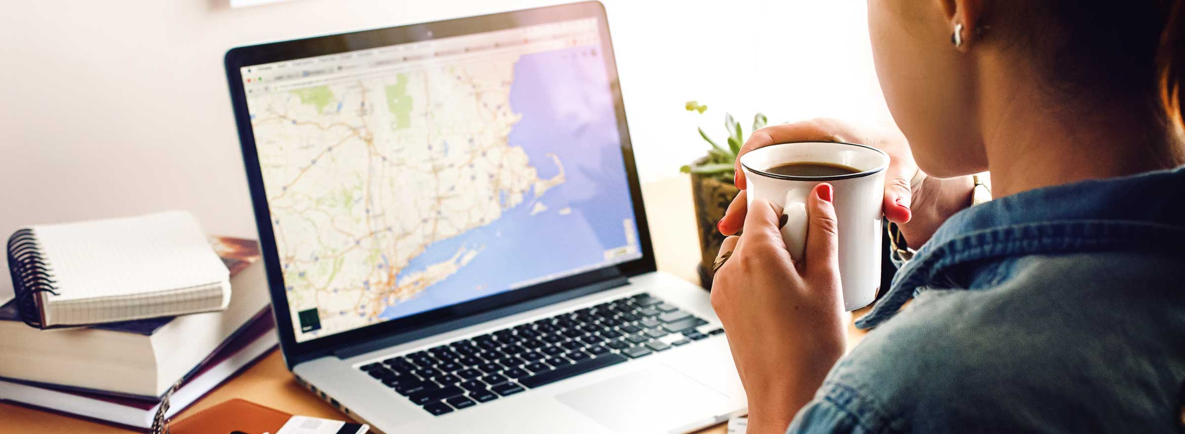 woman drinking coffee and looking at a map of the northeast US on a computer screen