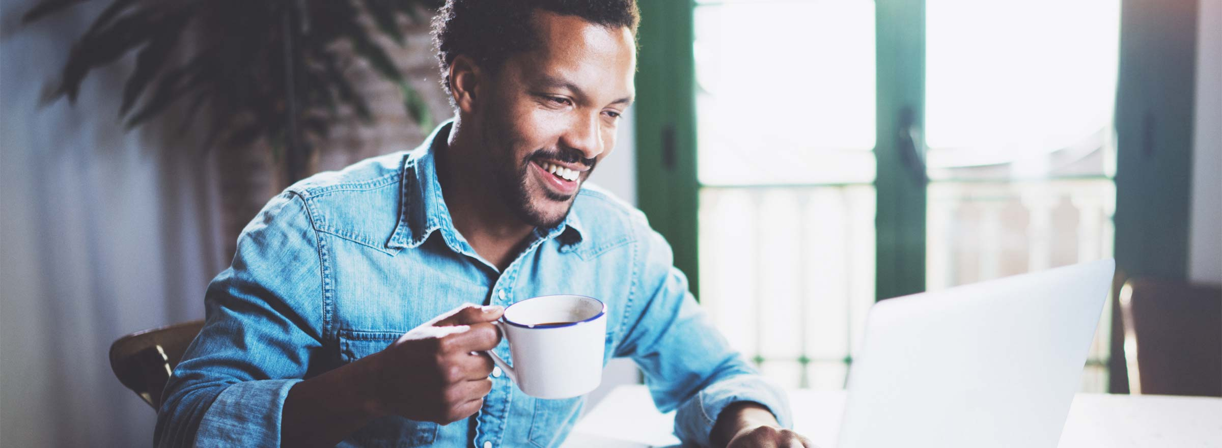 man drinking coffee and smiling at a computer