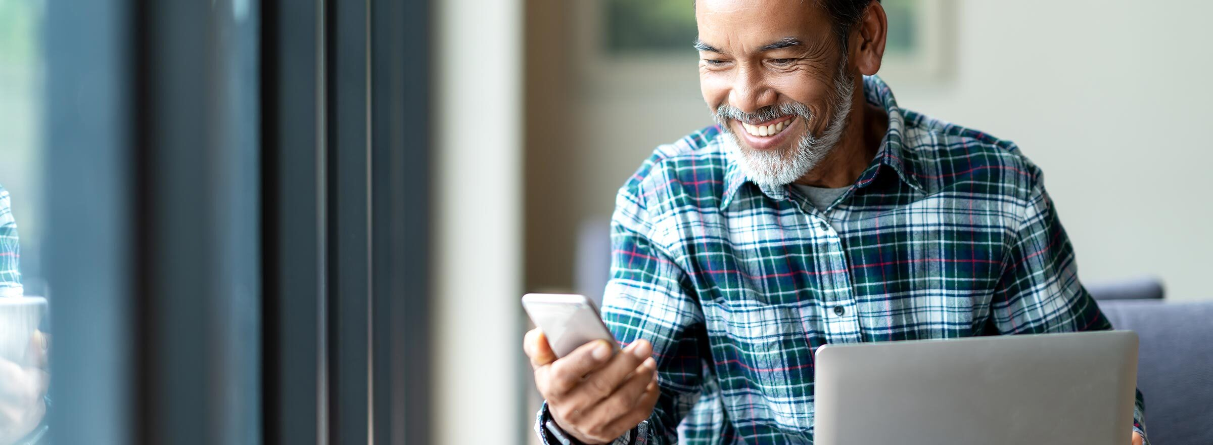 man sitting at laptop and smiling at smartphone