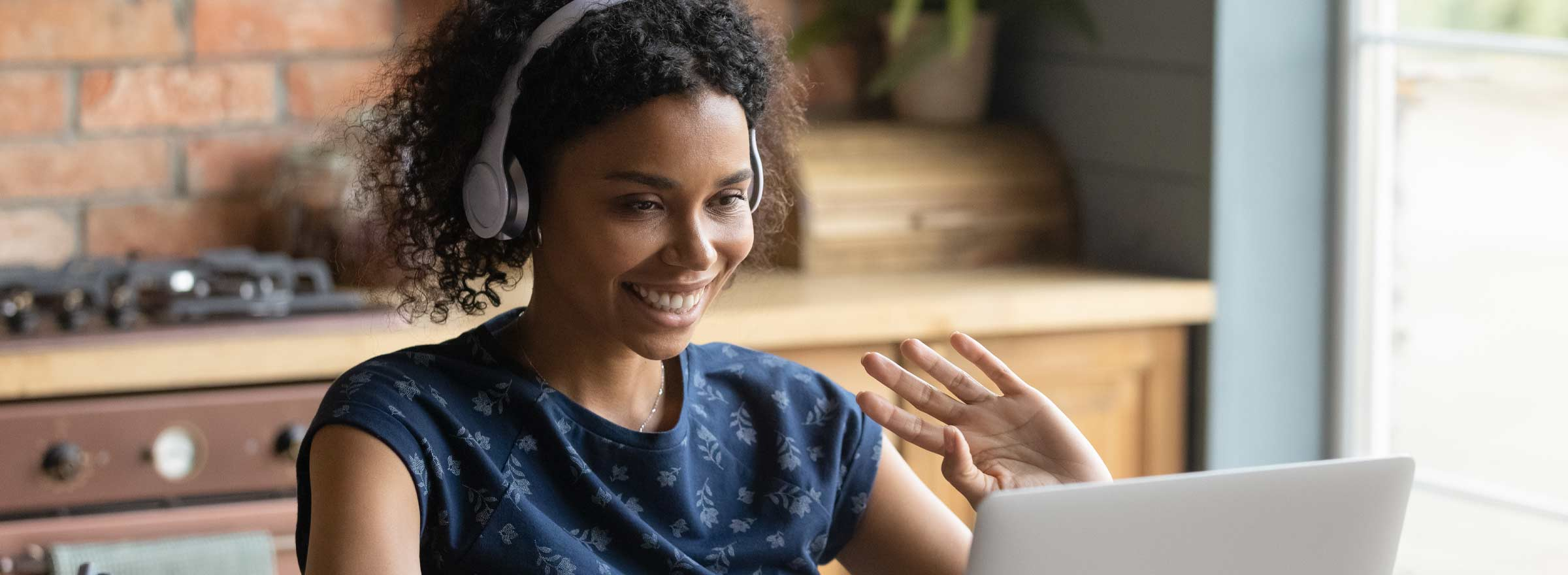 woman in headset waving at a computer screen