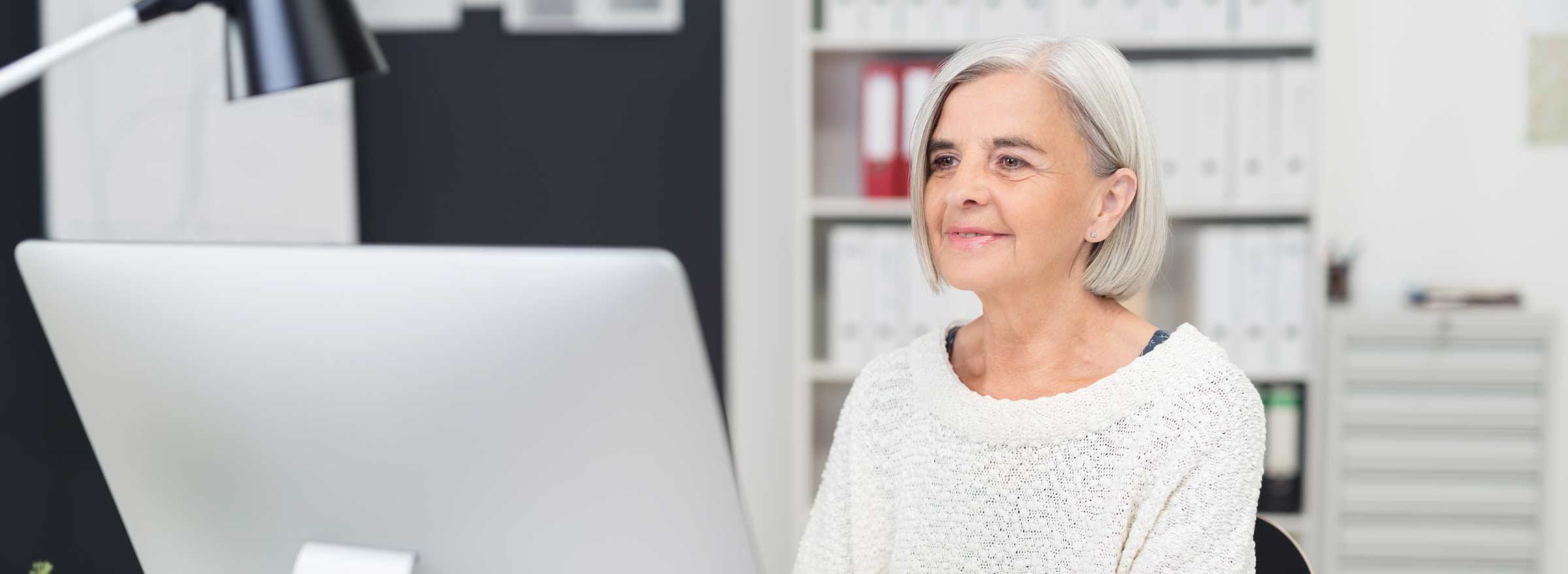 woman slightly smiling at a computer screen