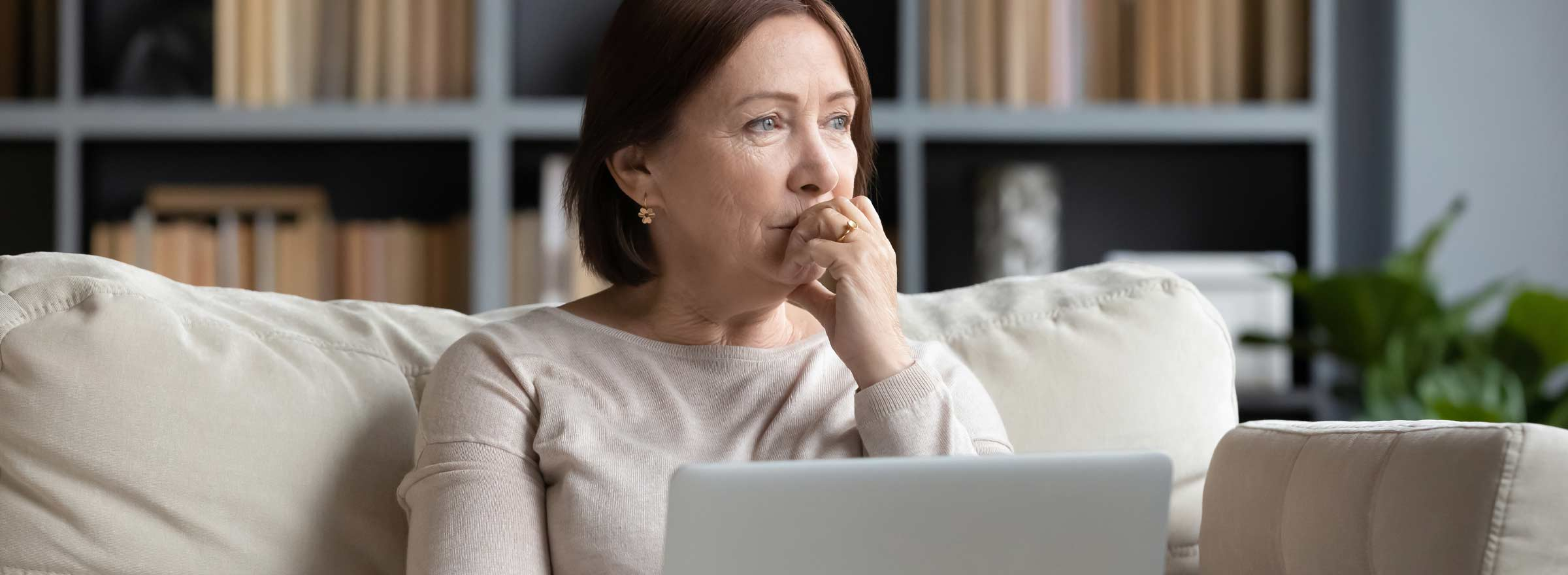 woman on a sofa holding a laptop and gazing into the distance