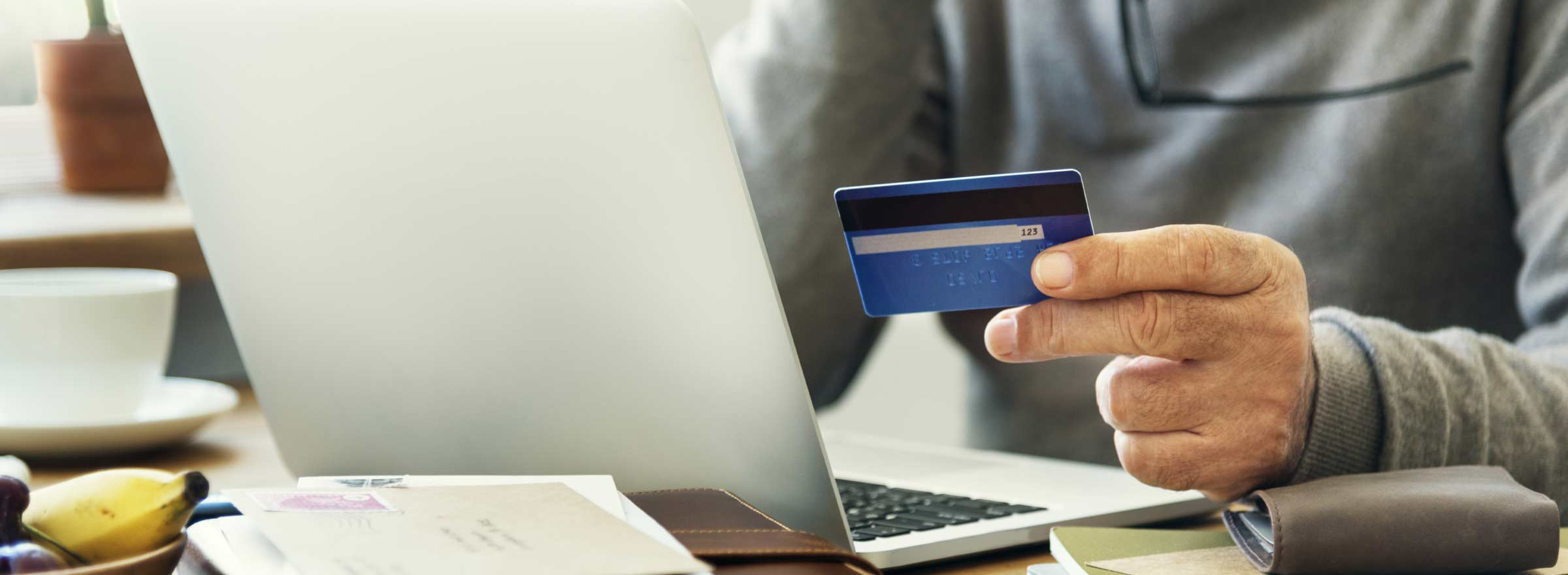 hand holding a credit card in front of a computer screen