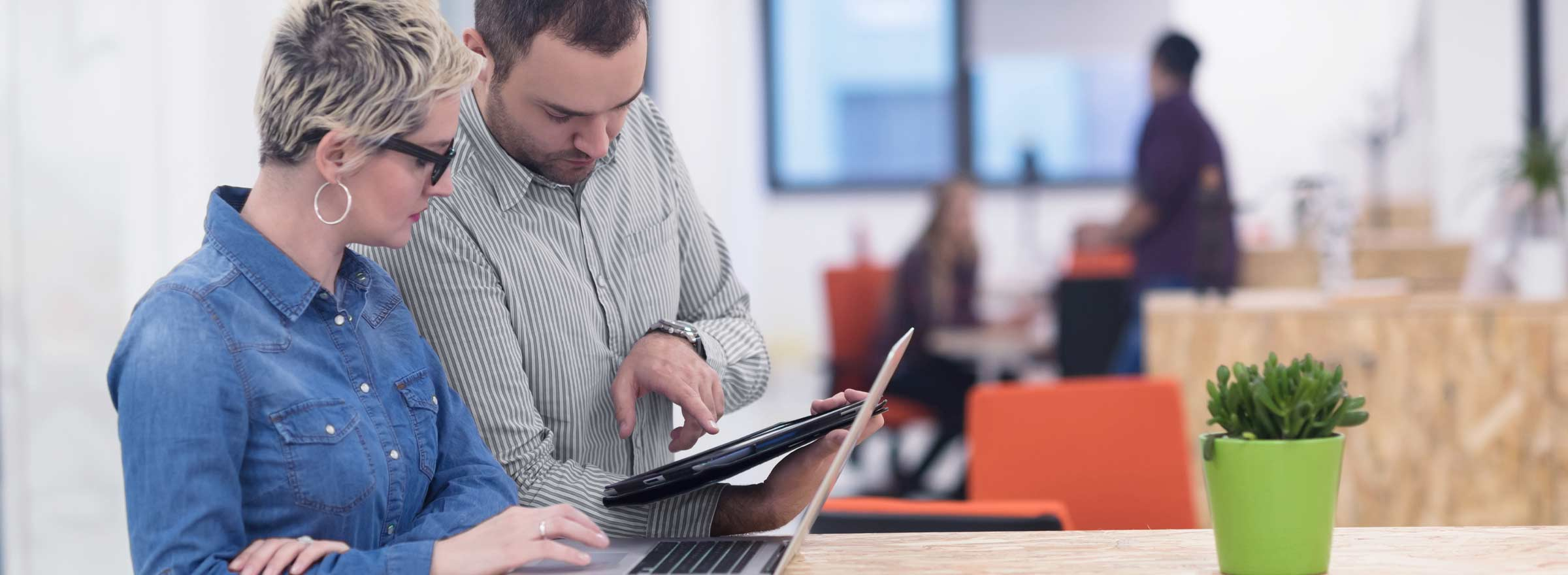 woman seated in front of laptop; man showing her something on a tablet